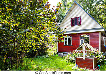 small wooden country house and well on backyard