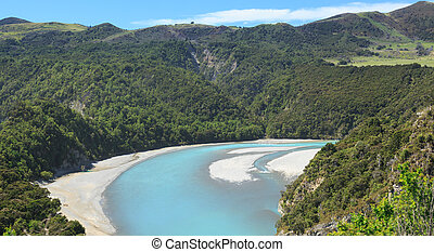 View from the train windows of Tranz Alpine railway over Waimakariri river gorge on journey to Arthurs Pass