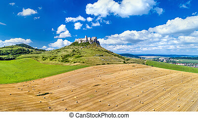 View of Spissky hrad and a field with round bales in Slovakia