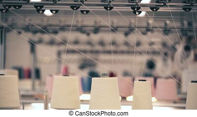 View of spools of white thread on knitting device - View...