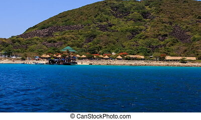view of stony beach with thatch umbrellas boat against hills...