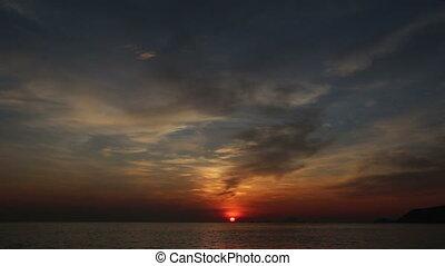 view of sun rise from behind horizon and clouds above sea -...