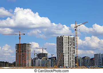 View of tall cranes and houses under construction.