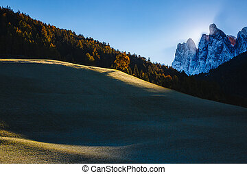 View of the alpine hill that glowing by sunlight. Location Funes valley, Dolomites. South Tyrol. Italy, Europe.