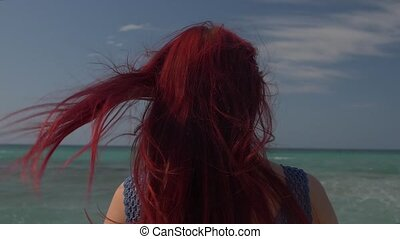 view of the back of a woman with red hair flying in the wind against the backdrop of the sea surf