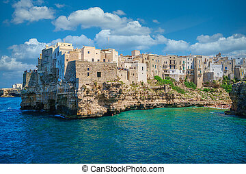 View of the beach and old houses of the tourist town of Polignano a Mare, Italy