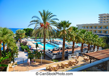 View of the beach resort hotel by the sea with palm trees next to the swimming pool, the lawn under a clear blue sky on the exotic island of Rhodes in Greece