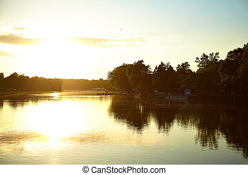 view of the beautiful lake in the park at sunset