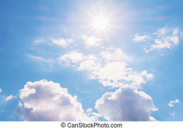 View of the blue sky with white cumulus clouds and the bright sun with rays and highlights.