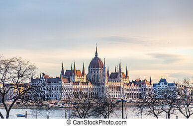 View of the building of the Hungarian Parliament illuminated by the rays of the setting sun. In Budapest, Hungary