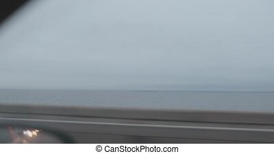 view of the car window while driving over a bridge on a cloudy day