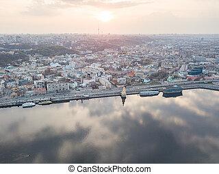 View of the Dnieper river, church of St. Nicholas on the water, River station and Naberezhno-Kreschatitska street on the sunset in Kiev, Ukraine.