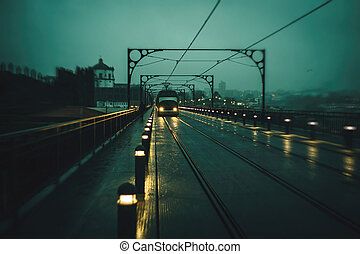 View of the Dom Luis I Iron Bridge and metro trains in cloudy weather at night, Porto, Portugal. Blurred image in motion.