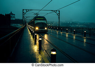 View of the Dom Luis I Iron Bridge and metro trains in cloudy weather at night, Porto, Portugal.
