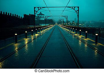 View of the Dom Luis I Iron Bridge and railway tracks at night, Porto, Portugal.