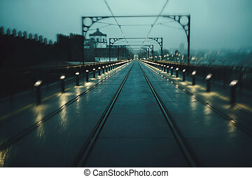 View of the Dom Luis I Iron Bridge in cloudy weather at night, in Porto, Portugal. Blurred image in motion.
