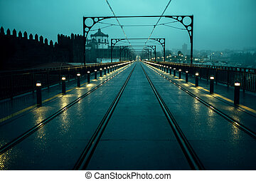 View of the Dom Luis I Iron Bridge in cloudy weather at night, in Porto, Portugal.