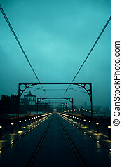 View of the Dom Luis I Iron Bridge in cloudy weather at night, Porto, Portugal.