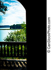 View of the forest landscape with a lake on a clear sunny day through the open door of a house with an ancient terrace.