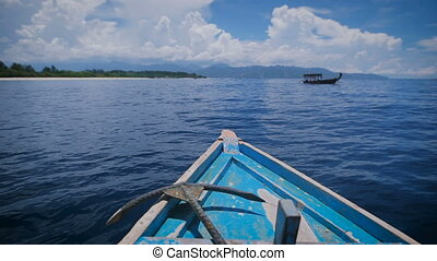 View of the front of the boat with metal anchor is moving rapidly into the distance in ocean. Blue salt water and beautiful sky with white cloud. Other motorboat floats nearby.
