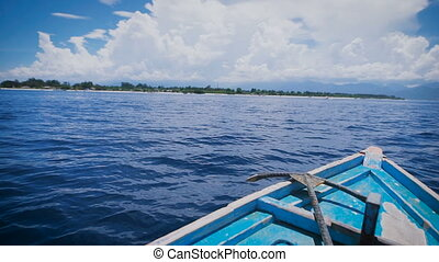 View of the front of the boat with metal anchor is moving rapidly into the distance in ocean. Blue salt water and beautiful sky with white cloud.
