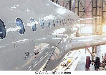 View of the fuselage of a passenger airliner with portholes and a wing with a landing gear in a repair hangar for aircraft.