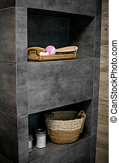 View of the gray shelves in the bathroom with bath accessories.