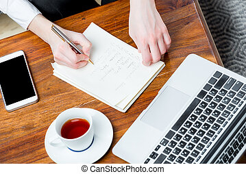 view of the hands at work, writing important information to the notebook