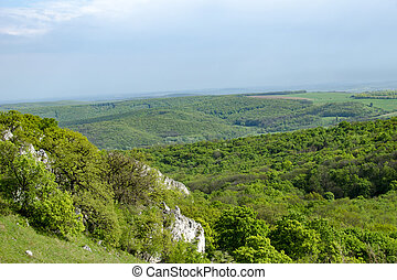 View of the hilly landscape of Palava with forests, rocks in South Moravia under a blue sky with clouds