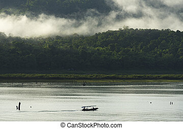 View of the lake with a boat roaming in Kanchanaburi, Thailand.