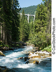 view of the Langwies Viaduct in the mountains of Switzerland near Arosa and a river below