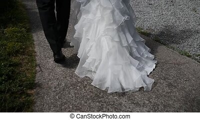 view of the legs, the bride and groom are walking, a beautiful train dress