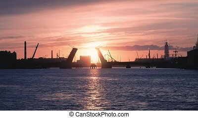 View of the lifted bridge across the Neva at sunset. Repair...