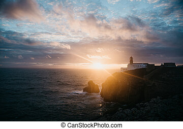 View of the lighthouse and cliffs at Cape St. Vincent in Portugal at sunset.