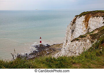 View of the lighthouse at Beachy Head in Sussex showing the tide out and the rocky beach leading out to the lighthouse.