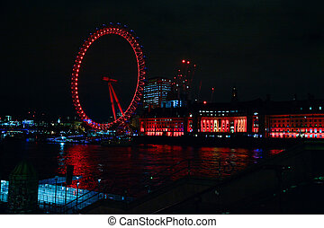 View of the London Eye at night on the South Bank of the River Thames, UK.