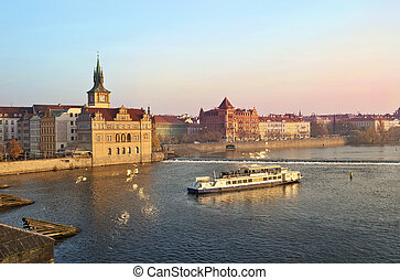 Tourists float on a boats on the Vltava river on the background a beautiful view over Prague Czech Republic