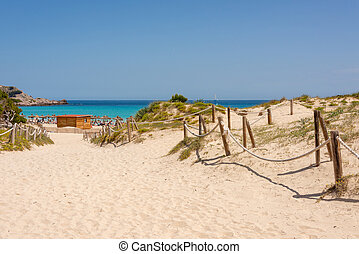 View of the Mediterranean Sea and sandy paths through the protected dunes to Cala Agulla beach on the Spanish holiday island of Mallorca