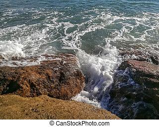 View of the Mediterranean sea breaking against the rocks