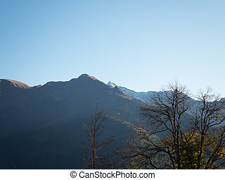 View of the mountain peaks in the backlight against the blue sky