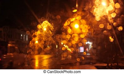 View of the night street through the windshield of the car. Traffic lights blink, lights shine. A car passes by