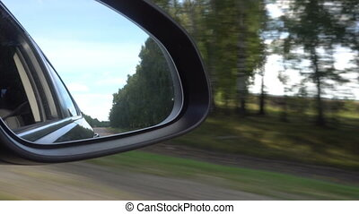 View of the road in the rearview mirror of a car.
