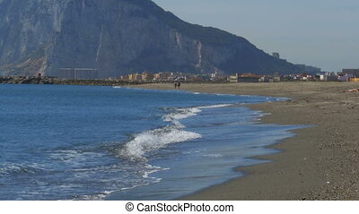 View of the Rock of Gibraltar and the beach with sea waves....
