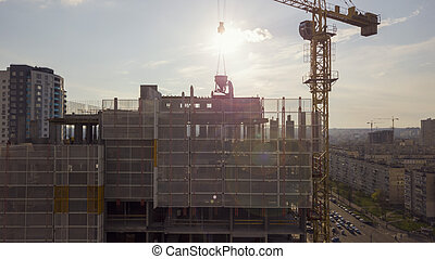 View of the roof of a high-rise building under construction with workers and the background of the city in the setting sun