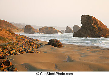View of the sandy beach and rocks during sunset in the Pacific Ocean