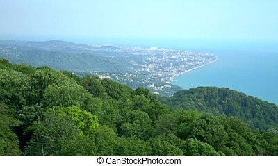 View of the sea coast and the city at the foot of a mountain range covered with forests. against the blue sky