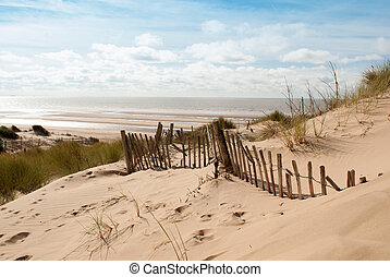 View of the sea from sand dune with old fence