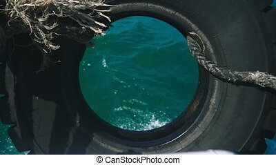 view of the sea through a tire wheel tied to the ship.