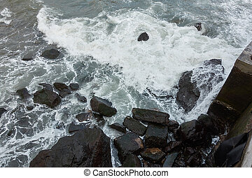 View of the sea with waves crashing on the rocks in Madeira, Portugal