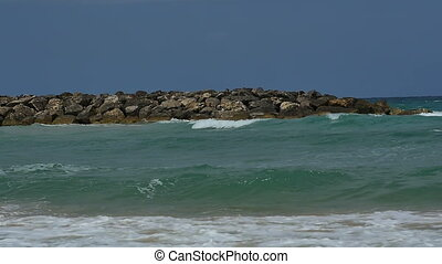 View of the seaside shore with waves calmly crashing on the sandy beach